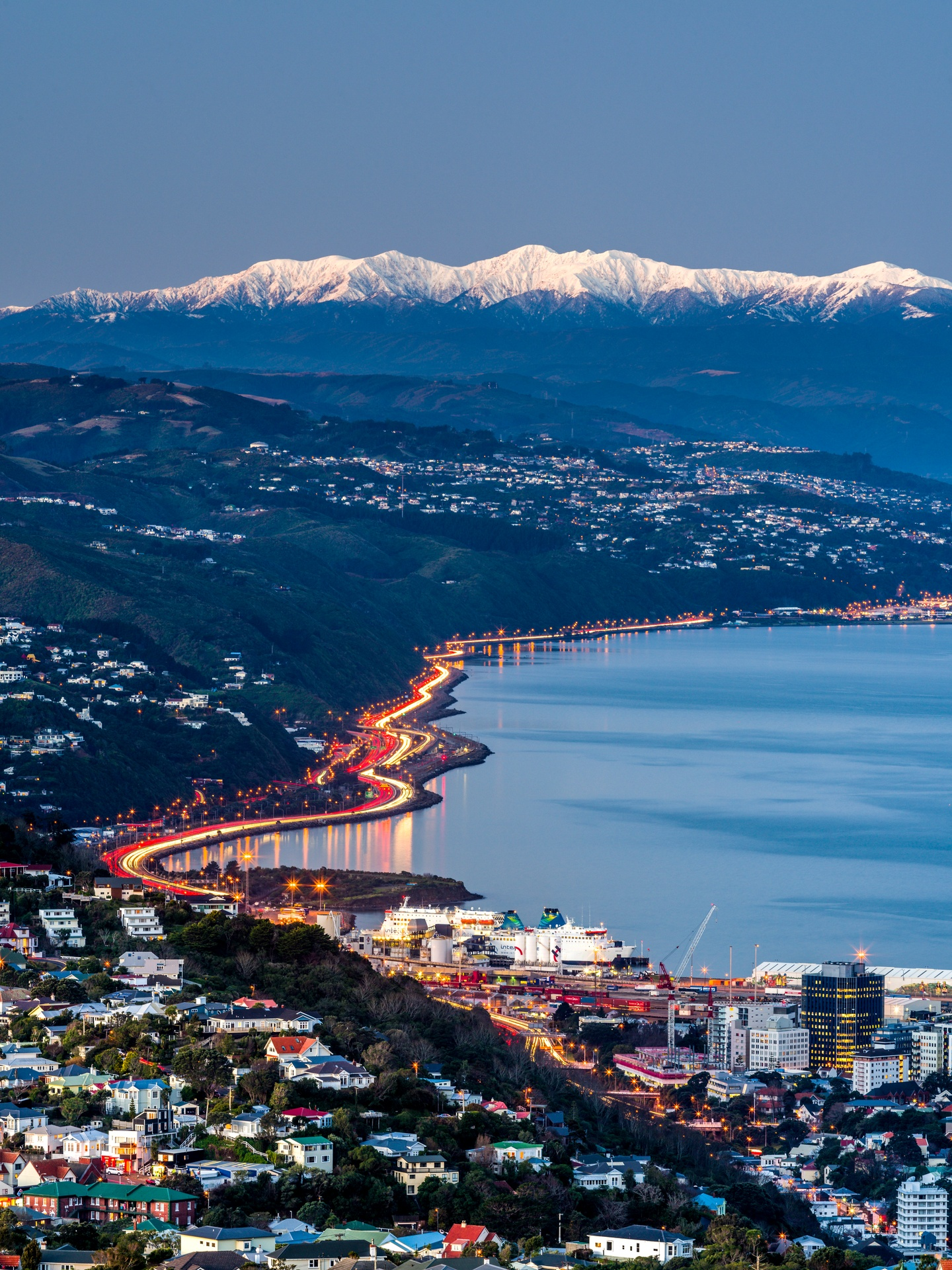 52793TC00-Wellington City and Harbour with snow covered Tararua Ranges above SH1 and SH2 traffic to the Hutt Valley. Wadestown, Thorndon and Kaiwharawhara in foreground. Winter dusk. Wellington, Wellington City District, North Island, NZ